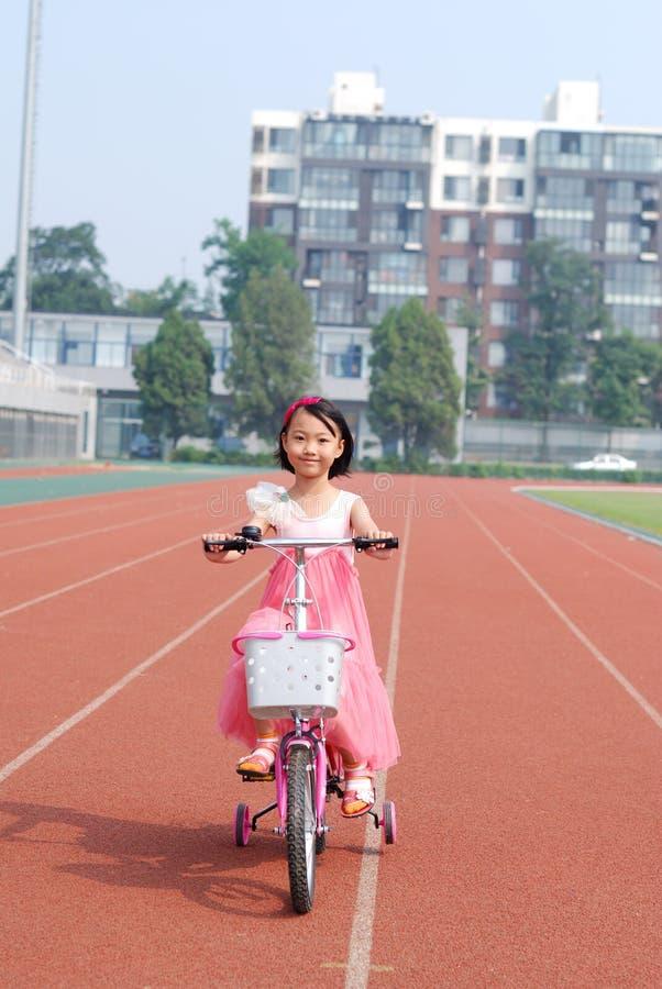 Asiatisk Liten Flicka Som Rider En Cykel Fotografering för Bildbyråer