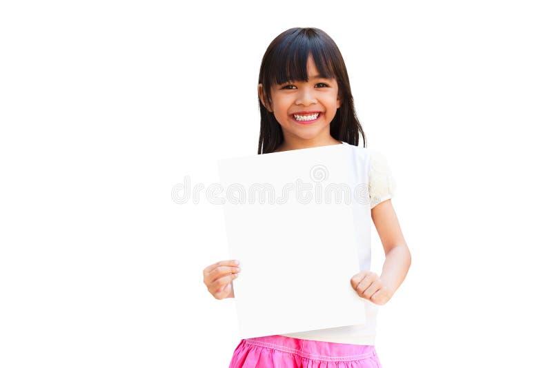 Asiatisk liten flicka som rymmer ett vitt ark av papper arkivfoto