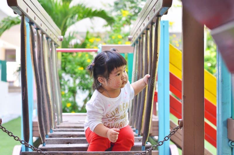 Asiatisk liten flicka som söker efter vännen som spelar på lekplatsthail royaltyfri fotografi