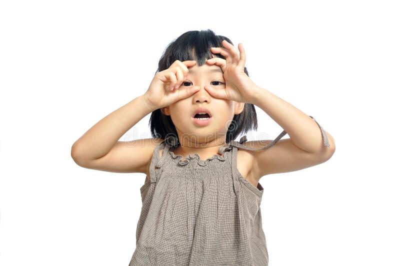 Asiatisk liten flicka som ser till och med imaginär binokulär isolerad nolla arkivfoton