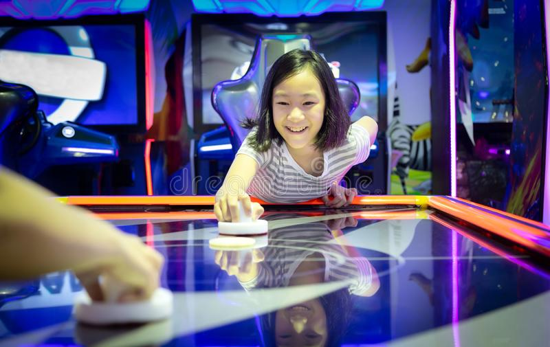 Asiatisk liten flicka som spelar gallerileken på datormaskinerna på shoppinggalleriauttagen, ferieaktiviteter av gullig barnlek royaltyfri bild
