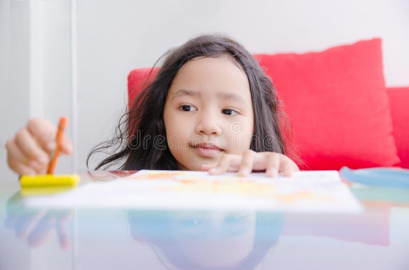 Asiatisk liten flicka som spelar med den shal selektiva fokusen för färgpennafärg royaltyfria foton