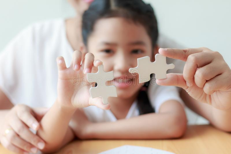 Asiatisk liten flicka som spelar pusslet med hennes moder för fami royaltyfri bild