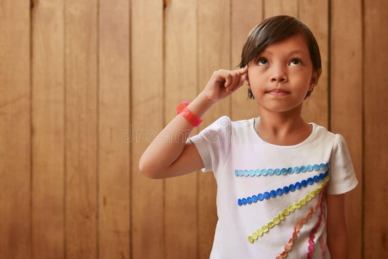 Asiatisk liten flicka som tänker på wood bakgrunder fotografering för bildbyråer