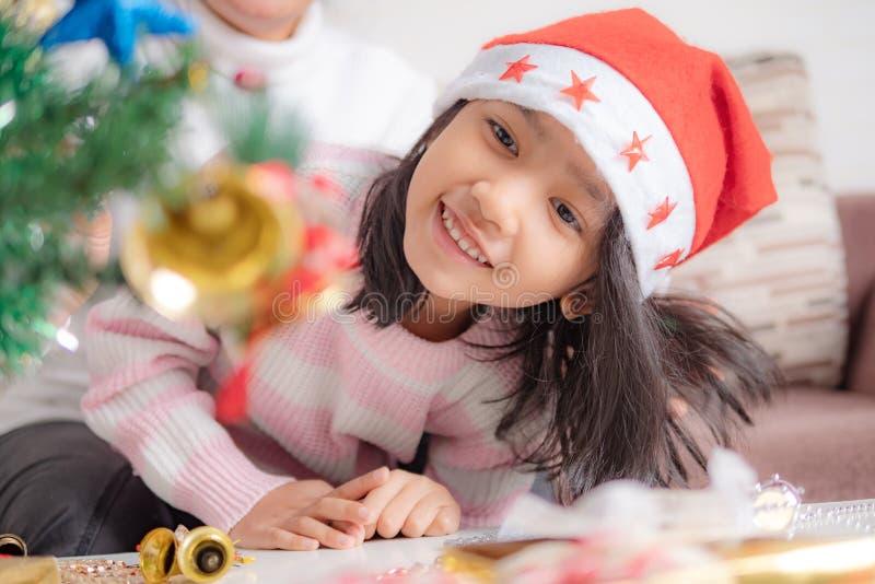 Asiatisk liten flickablick på julgranen och leendet med happ arkivbild