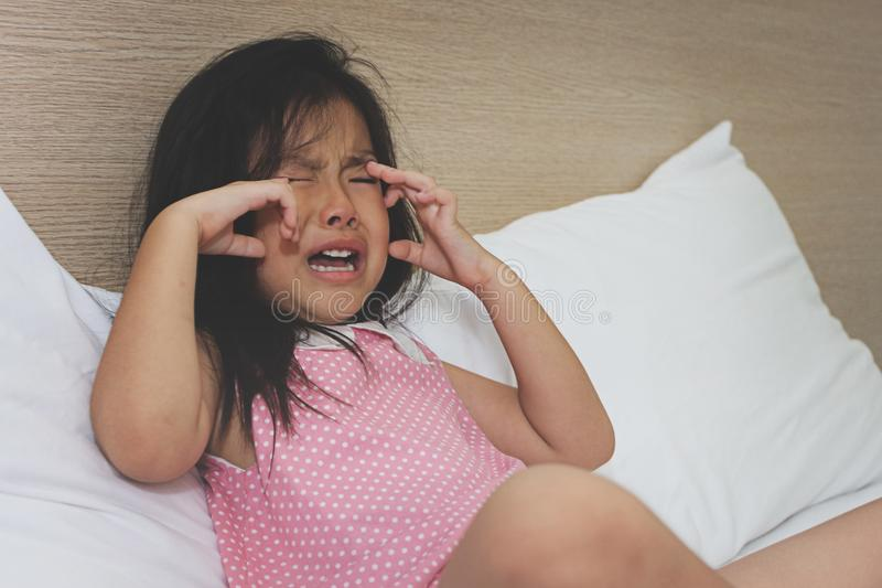 Asiatisk liten flickagråt på säng arkivbild