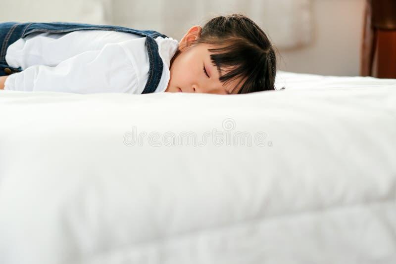 Asiatisk liten flickalögn och sömn på vit säng med villkoret av fridsamt och att koppla av tid royaltyfri fotografi