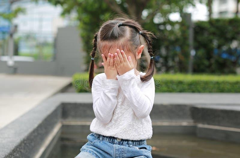 Asiatisk liten flickaräkning hennes framsida med hennes händer royaltyfria bilder
