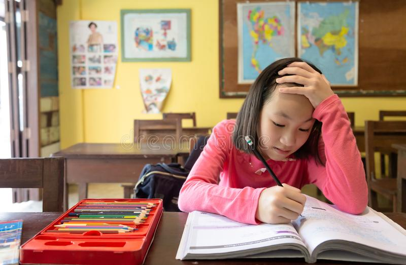 Asiatisk liten flickastudent som använder idén, tänka och meditationen att göra läxa i klassrumet, stående av att studera för bar royaltyfria bilder