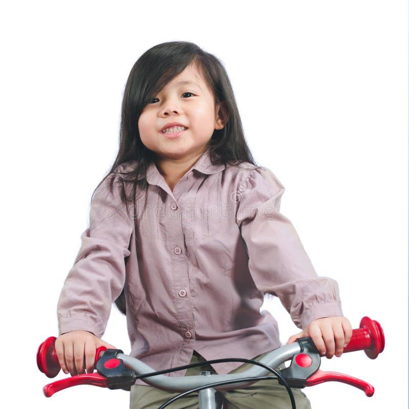 Asiatisk liten gullig flicka som ler och rider på cykeln som isoleras på royaltyfri bild