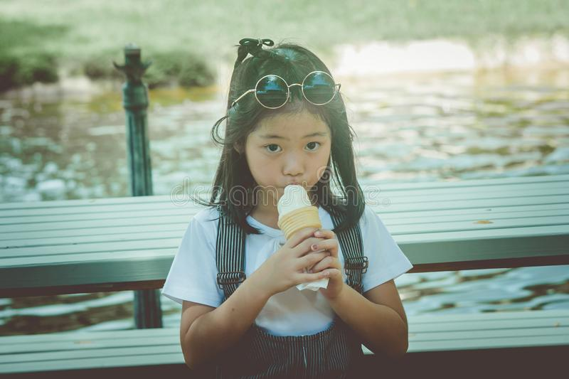 Asiatisk liten gullig flicka som sitiing på träbänk och äter glass på parkera arkivbilder