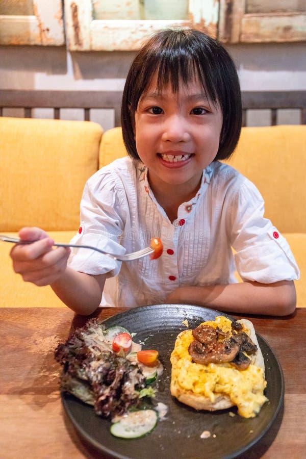 Asiatisk liten kinesisk flicka som äter frukosten arkivbilder