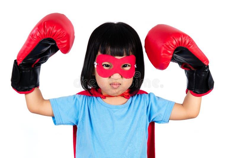 Asiatisk liten kinesisk flicka som bär dräkten för toppen hjälte med boxning arkivbilder
