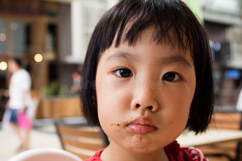 Asiatisk liten kinesisk flicka som gör en röra med mat arkivbilder