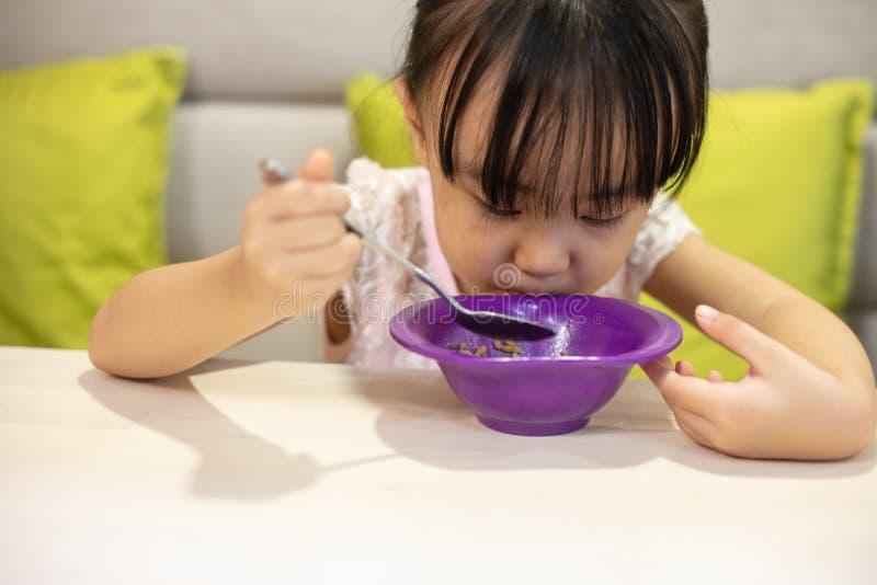 Asiatisk liten kinesisk flicka som har lunch arkivbilder