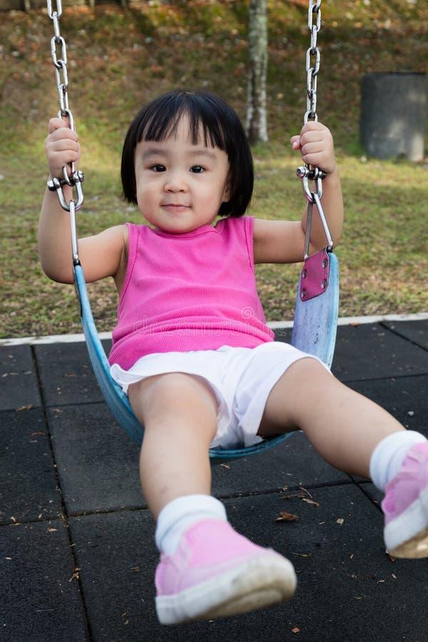 Asiatisk liten kinesisk flicka som spelar gunga fotografering för bildbyråer