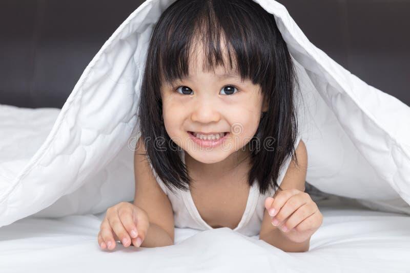 Asiatisk liten kinesisk flicka som spelar på sängen arkivbilder