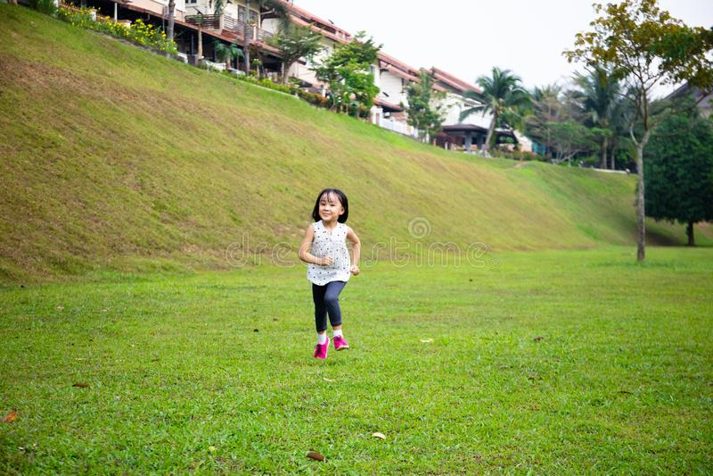 Asiatisk liten kinesisk flicka som springer lyckligt royaltyfria bilder
