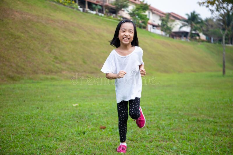 Asiatisk liten kinesisk flicka som springer lyckligt arkivbild