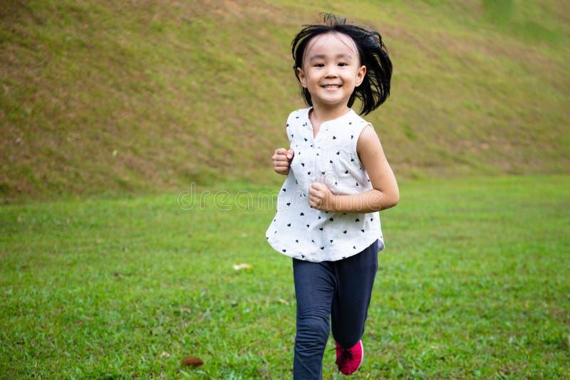 Asiatisk liten kinesisk flicka som springer lyckligt royaltyfri bild