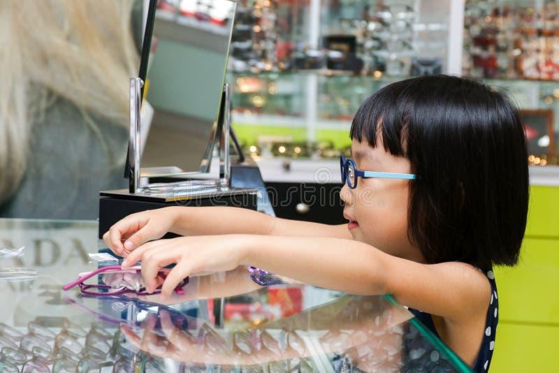 Asiatisk liten kinesisk flicka som väljer exponeringsglas arkivbild