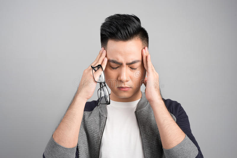 Asiatisk man för frustrerad affär med en huvudvärk - som isoleras över gr fotografering för bildbyråer