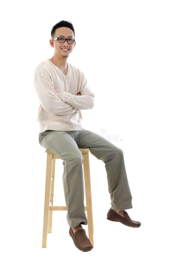 Asiatisk man för full huvuddel som sitter på en stol fotografering för bildbyråer