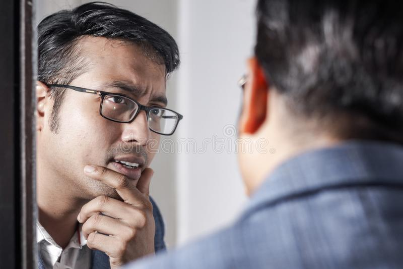 Asiatisk man i dräkt som framme sköter hans utseende av en spegelskönhet som utformar livsstil arkivbilder