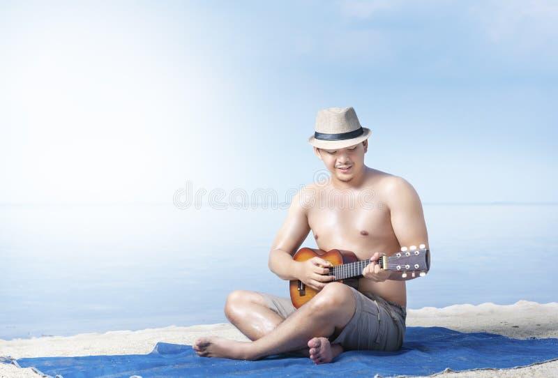 Asiatisk man i hatten som sitter och spelar gitarren på mattan i strand royaltyfri foto