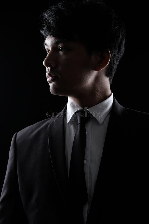 Asiatisk man i svart formell dräkt i mörkret arkivfoto