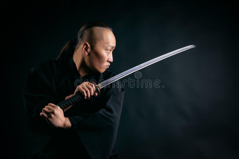Asiatisk man med ett svärd i hans händer i en svart ämbetsdräkt mot en svart bakgrund royaltyfri fotografi
