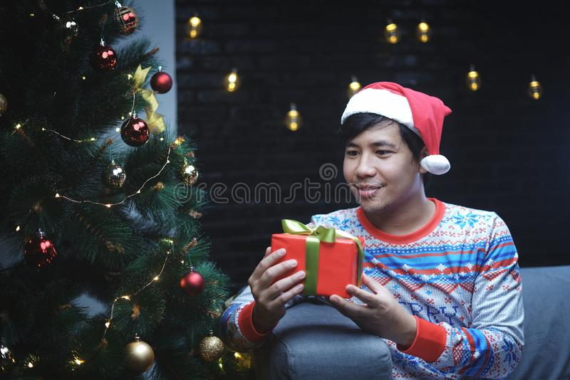 Asiatisk man med juldräkten som rymmer julgåvan som sitter bredvid julgranen royaltyfri foto