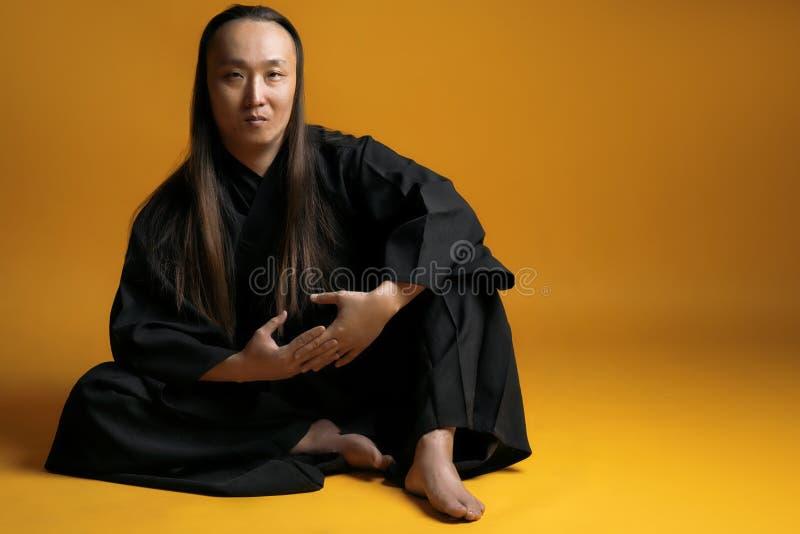 Asiatisk man med långt hår i en svart kimono på en gul bakgrund royaltyfria bilder