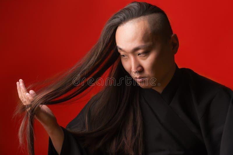 Asiatisk man med långt tjockt hår på en röd bakgrund arkivbild