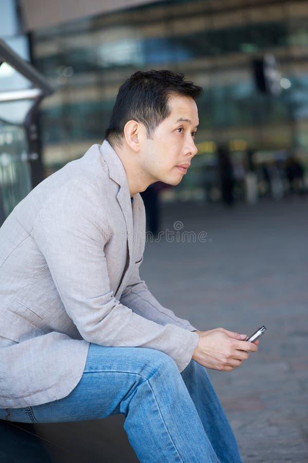 Asiatisk man med mobiltelefonen fotografering för bildbyråer
