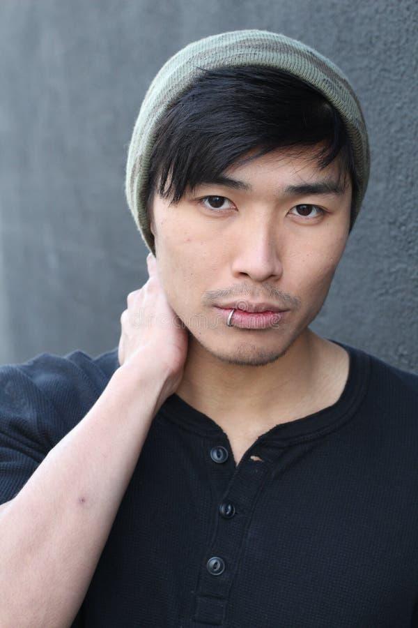 Asiatisk man med piercing och beanien arkivbild