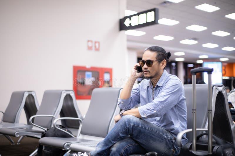 Asiatisk man med ryggsäckhandelsresanden som använder den smarta mobiltelefonen för den videopd appellen och tar på en flygplats arkivbilder