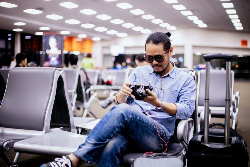 Asiatisk man med ryggsäckhandelsresanden som kontrollerar bilden på kamera på en flygplats royaltyfri fotografi