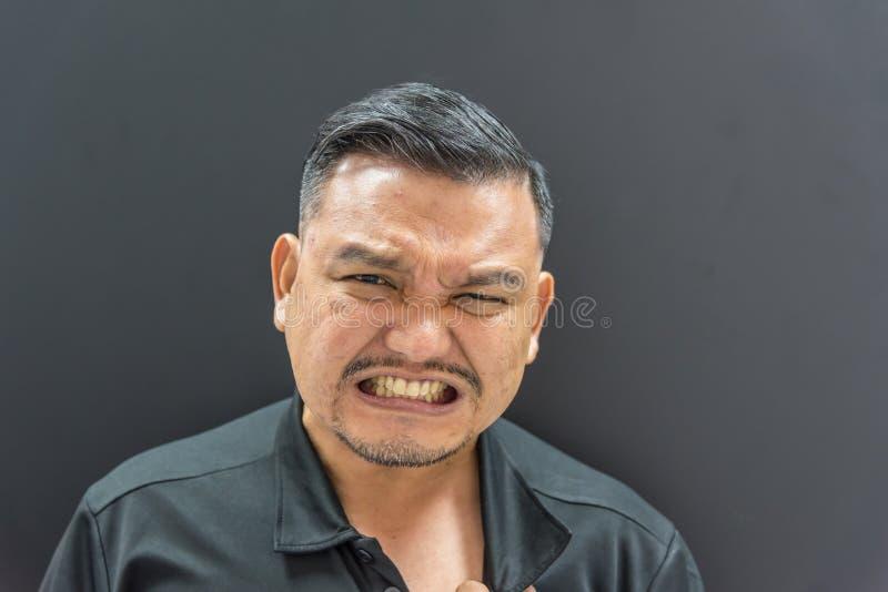 Asiatisk man som är smärtsam från sjukdomhjärtinfarkt arkivbild