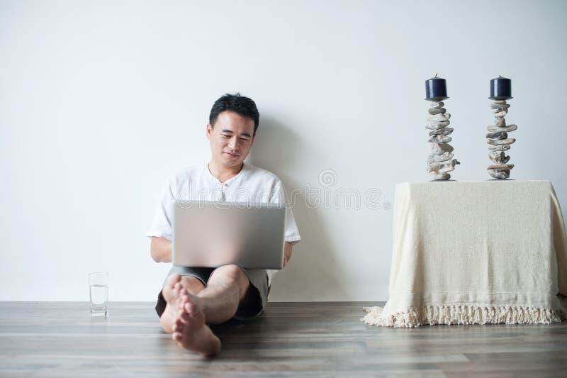 Asiatisk man som använder bärbar dator arkivfoton