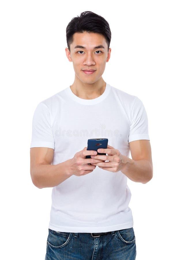 Asiatisk man som använder mobiltelefonen för att spela leken royaltyfri fotografi