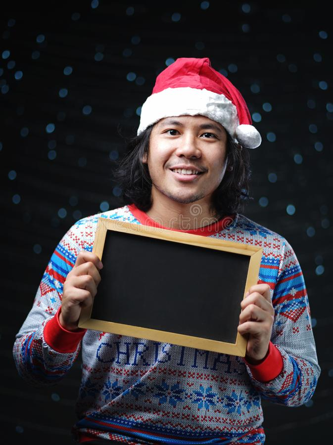 Asiatisk man som bär Santa Hat och jultröjan som rymmer Blackb royaltyfri foto
