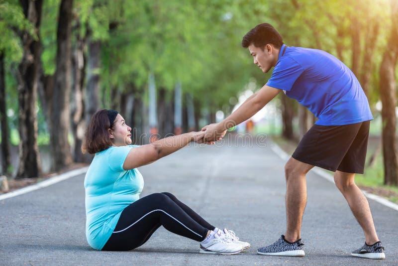 Asiatisk man som drar handen av den feta kvinnan som tröttade och sammanträde på gro arkivbilder