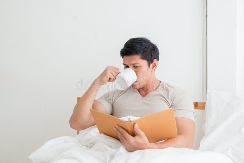 Asiatisk man som dricker en kopp kaffe eller en frukost i säng arkivfoton