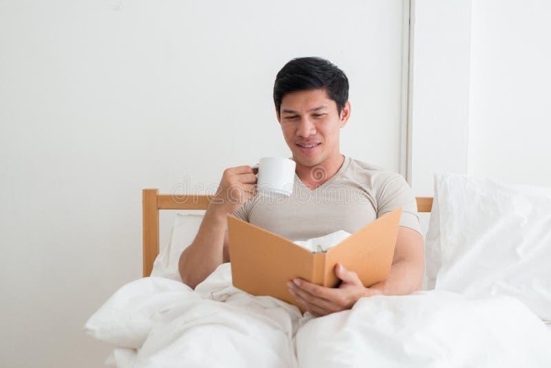 Asiatisk man som dricker en kopp kaffe eller en frukost i säng royaltyfri bild