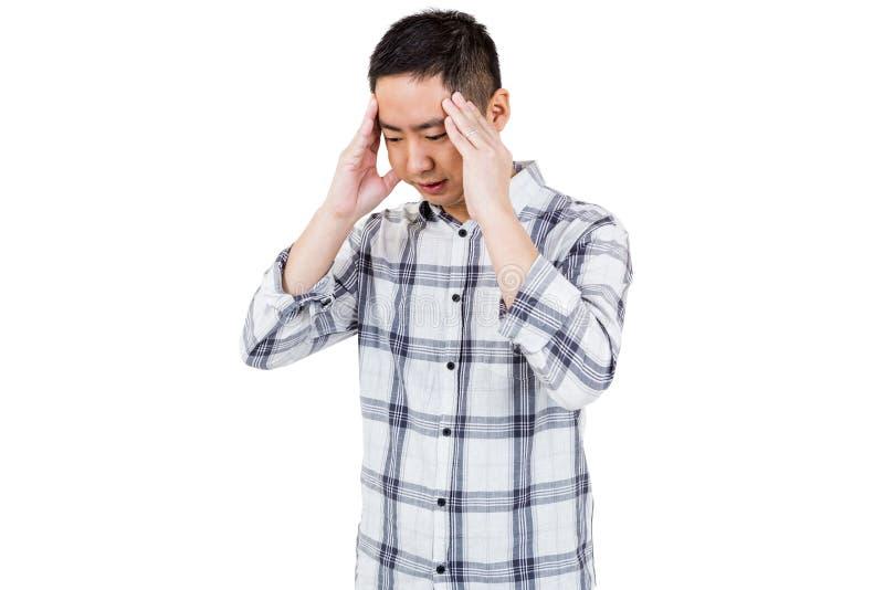 Asiatisk man som får en huvudvärk arkivfoto