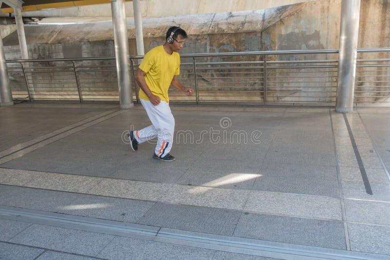 Asiatisk man som joggar med hörlurarmusik i staden arkivbilder