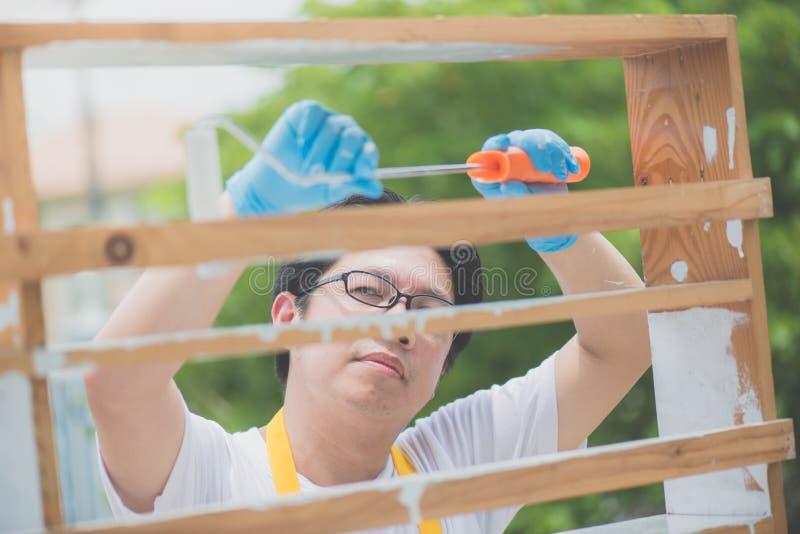 Asiatisk man som paiting trähyllan utomhus fotografering för bildbyråer