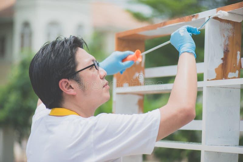 Asiatisk man som paiting trähyllan utomhus royaltyfri foto