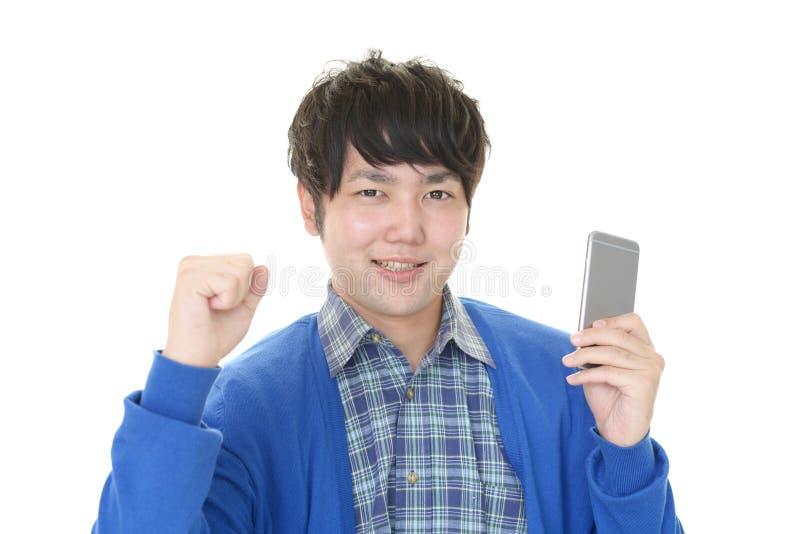 Asiatisk man som rymmer en smart telefon royaltyfri foto
